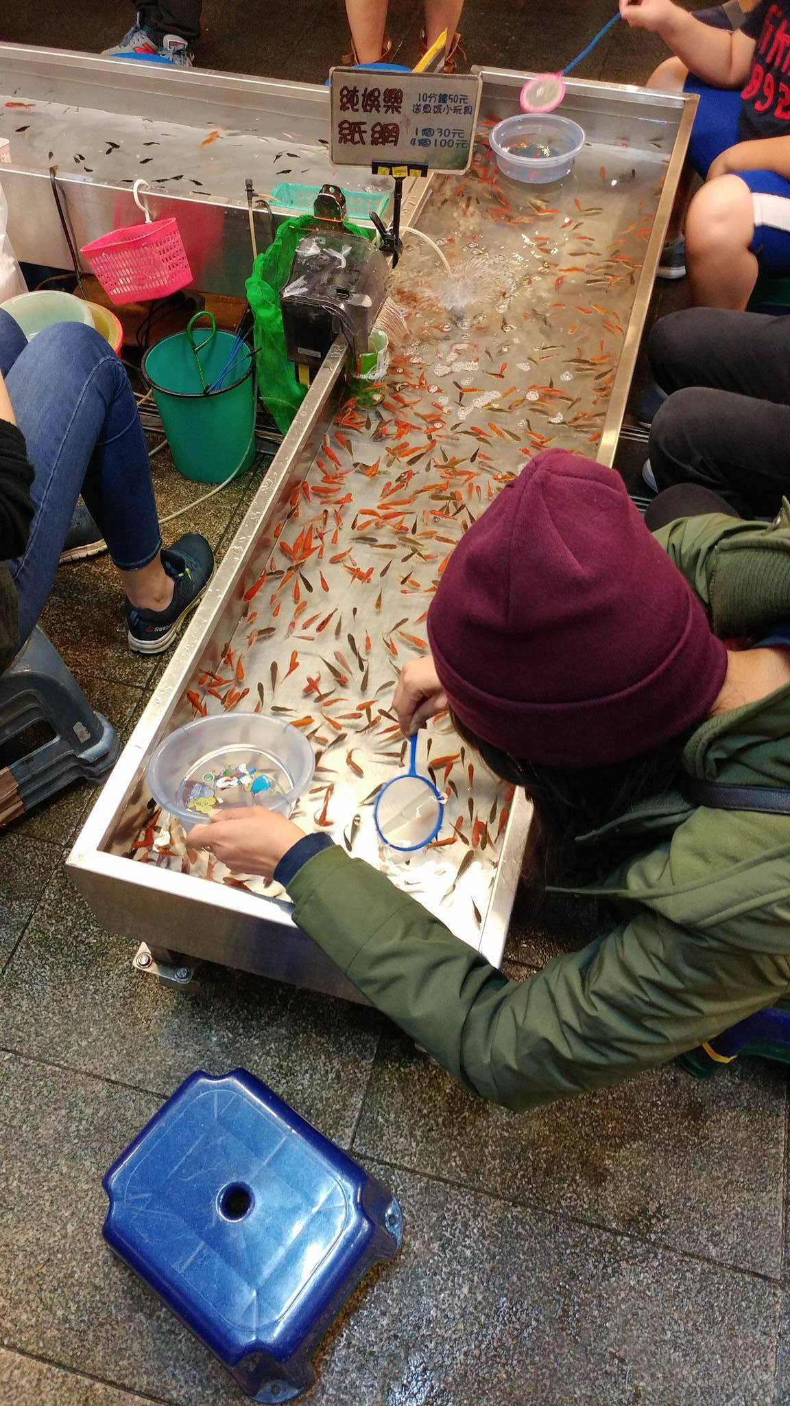 Playing a fishing game at the Shilin Night Market, Taipei, Taiwan - Kay