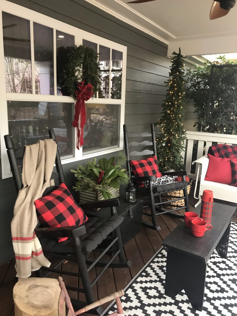 Marietta Pilgrimage - House 6; front porch with two black rocking chairs, a black table with a red thermos and two red cups, and the area is decorated with a Christmas tree in the corner and a wreath on the window