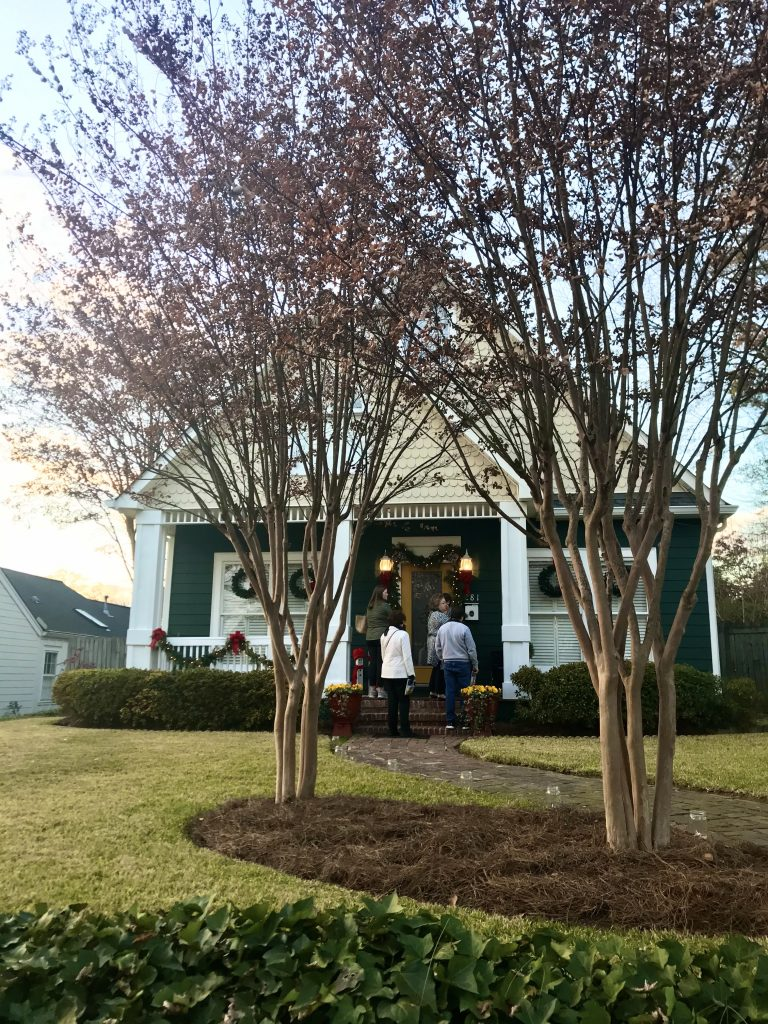 Marietta Pilgrimage - House 4; green house with yellow door and garland draped along the front porch and wreaths on the windows