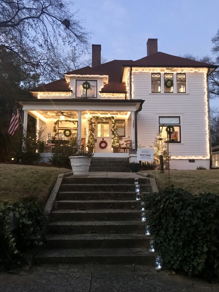 Marietta Pilgrimage - House 1, white house with clear Christmas lights around the house and wreaths on the windows and garland on the door