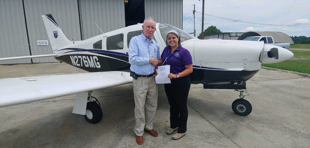Victoria and an older gentlemen standing in front of a small plane. They are shaking hands while they grasp Victoria's certificate with their other hands, holding it for the camera to capture. Victoria is wearing a purple collared shirt, black pants, and beige shoes. The gentleman is wearing a light blue long-sleeved collared shirt, khaki pants, and brown shoes.