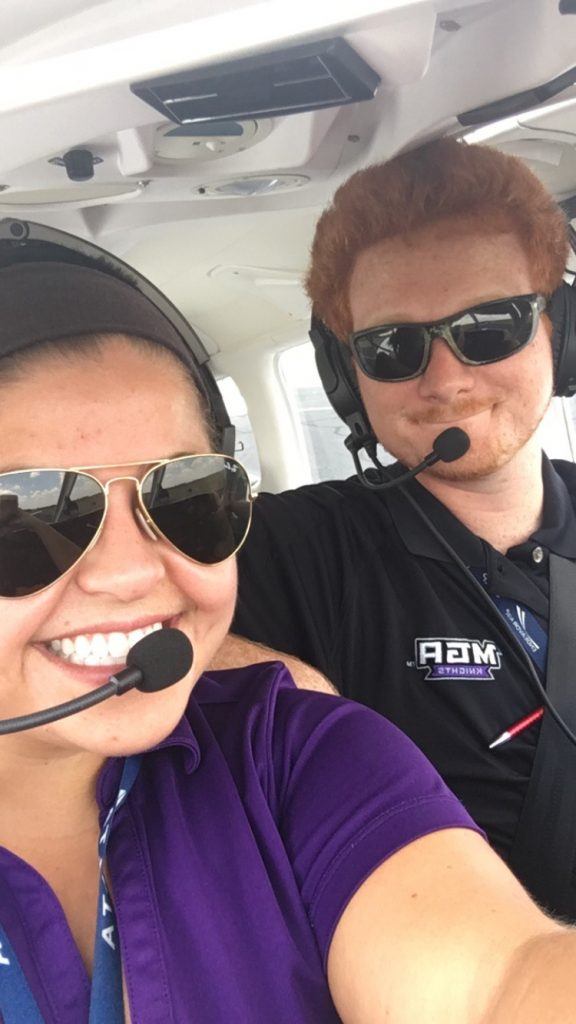 Victoria, smiling at the camera with her headset on wearing a purple collared shirt, with her instructor who is soft smiling at the camera with his headset on. He is wearing a black collared shirt. They are both wearing dark sunglasses.