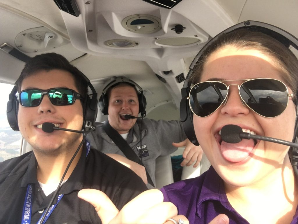 Victoria and her two guy friends, all wearing headsets. Victoria is wearing a purple collared shirt, dark sunglasses, and holding up an aloha sign with her hand, while smiling and sticking out her tongue. The guy next to her is smiling, wearing dark sunglasses, and wearing a black collared shirt with a blue lanyard. The guy in the back is smiling with his mouth open and wearing a gray collared shirt.