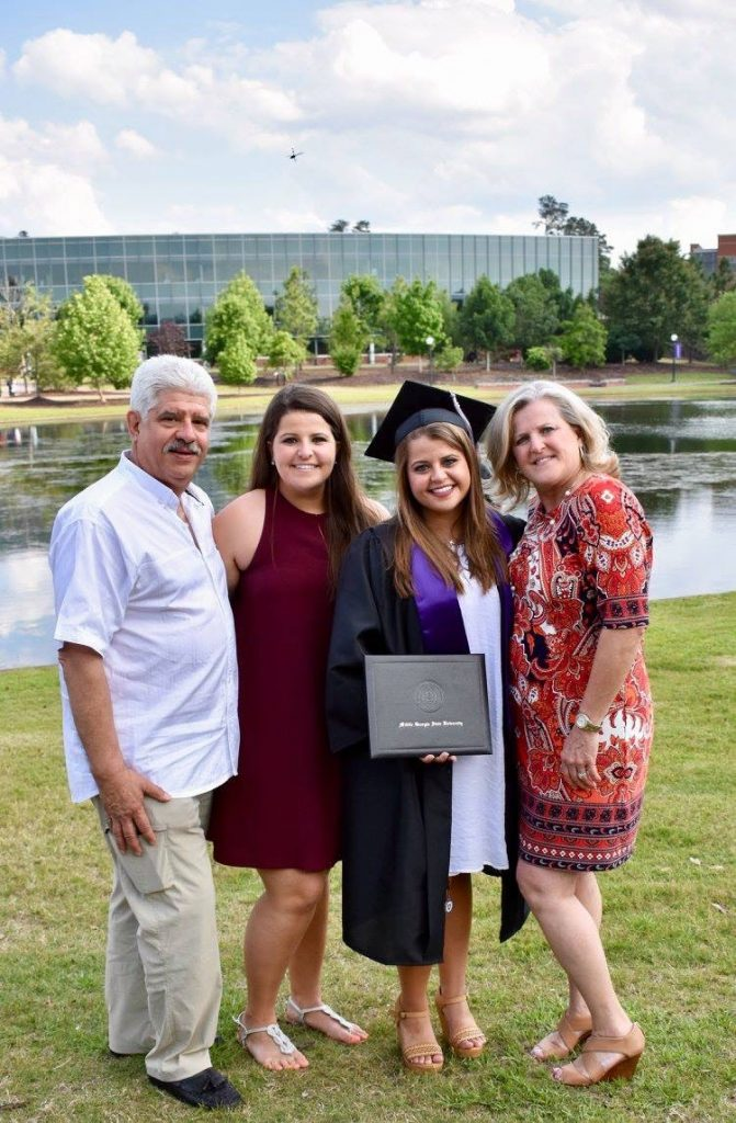 Victoria standing with her family after graduation. The group of 4 is all dressed up, with Victoria in a cap and gown holding her diploma.