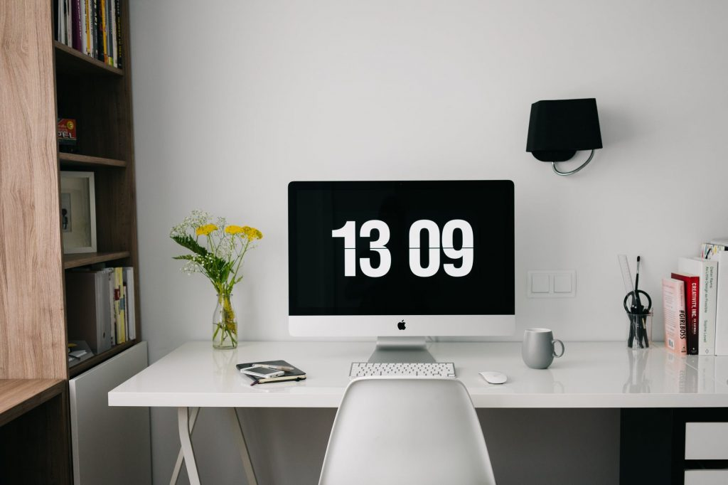 Silver iMac on white desk. There is a bookshelf to the left of the desk, containing various pictures and a picture frame. There is a vase of yellow flowers on the desk, a black and white journal, keyboard in front of the monitor, a mouse to the right of the keyboard, and a coffee mug to the right of the mouse. Represents how Imposter Syndrome shows up in my working life.