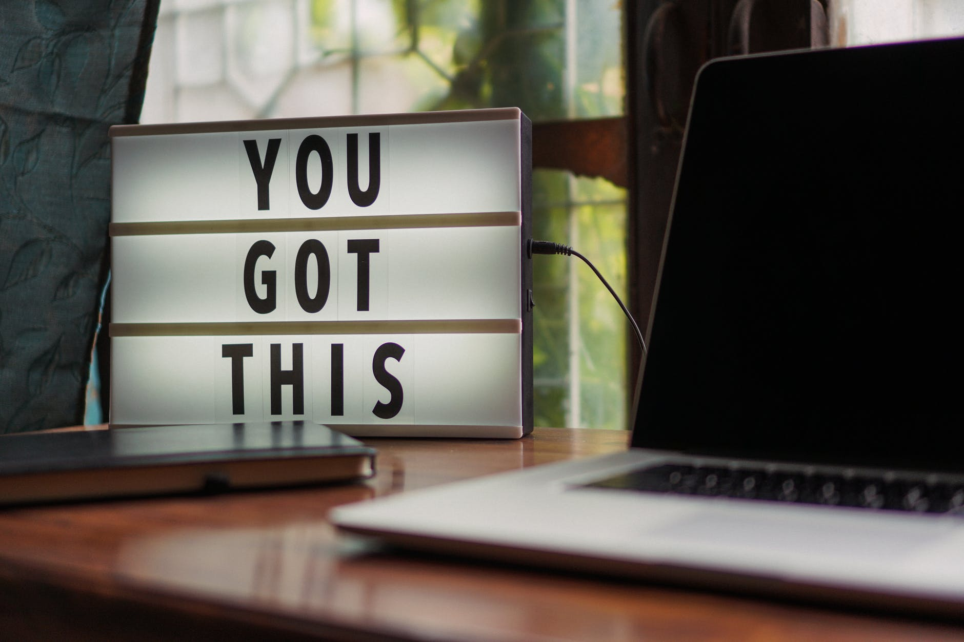 Macbook on a brown desk with a lighted up sign in the background to the left, stating you got this in the frame. Used to represent even though we deal with Imposter Syndrome, we are enough.