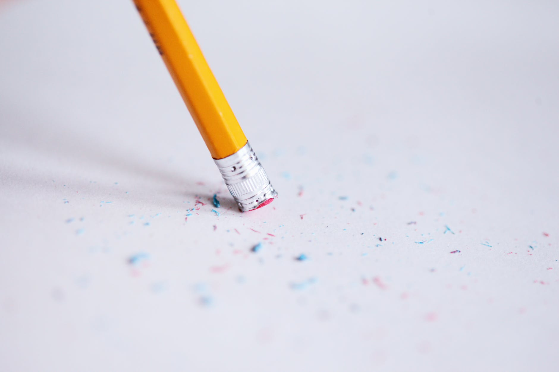 The eraser end of a number two pencil, with eraser shavings scattered around the end on the white piece of paper. Used to represent that mistakes are learning opportunities when dealing with Imposter Syndrome.