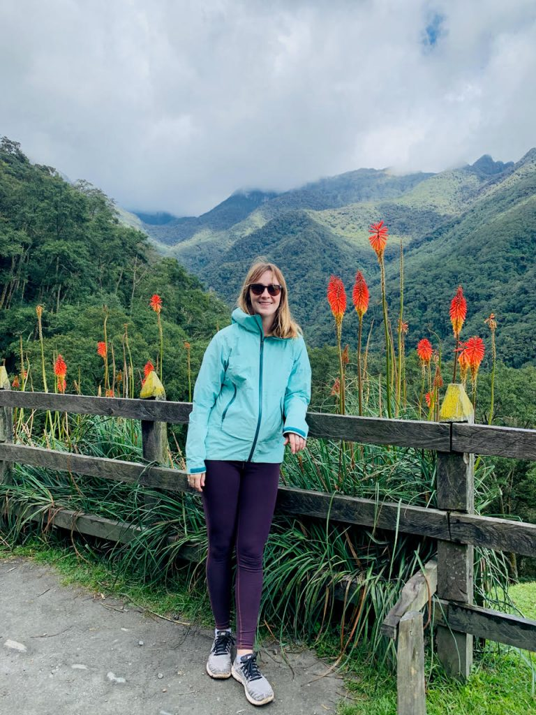 Alia is standing in a National Park in Colombia. She is wearing purple pants, a light blue rain jacket, and dark sunglasses while smiling into the camera. There are beautiful mountains behind her in the distance and brightly colored plants, in the shades of red, orange, and yellow directly behind her.