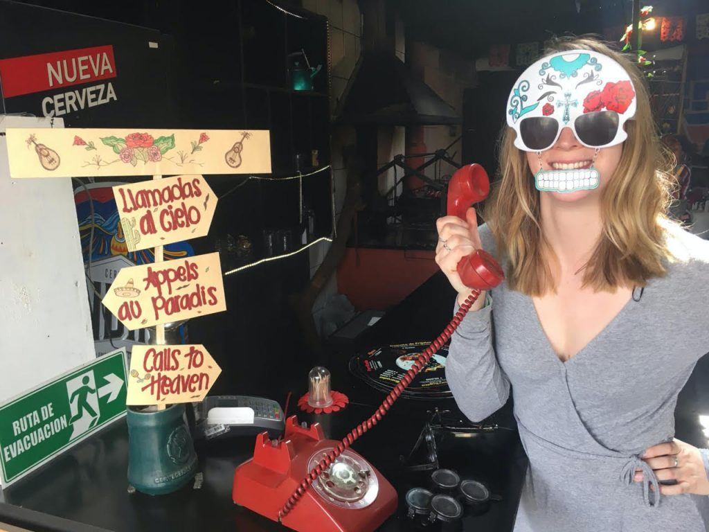 Alia in a restaurant in Colombia. She is wearing a white mask that is decorated in the fashion of Day of the Day, with a row of paper teeth hanging down from the mask. Alia is wearing a gray dress, has one hand propped on her hip, and the other hand is holding a red receiver of an old fashion dial phone.