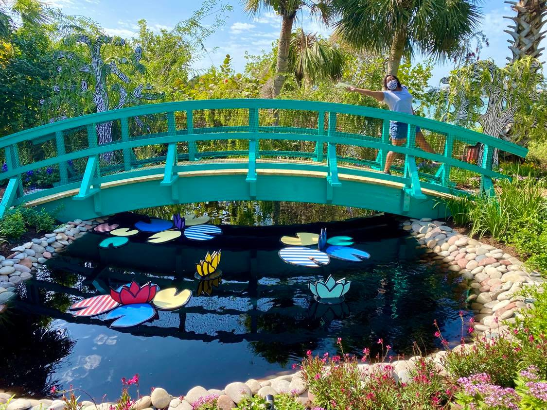 Larissa walking across a green bridge in the Downtown Sarasota Botanical Garden, that has painted wooden lilypads and lotus flowers of various colors during her weekend in Sarasota
