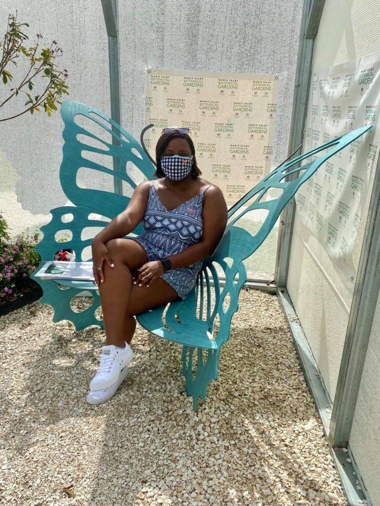 Larissa sitting in a butterfly chair in the butterfly house at the Historic Spanish Point Botanical Gardens during her weekend in Sarasota