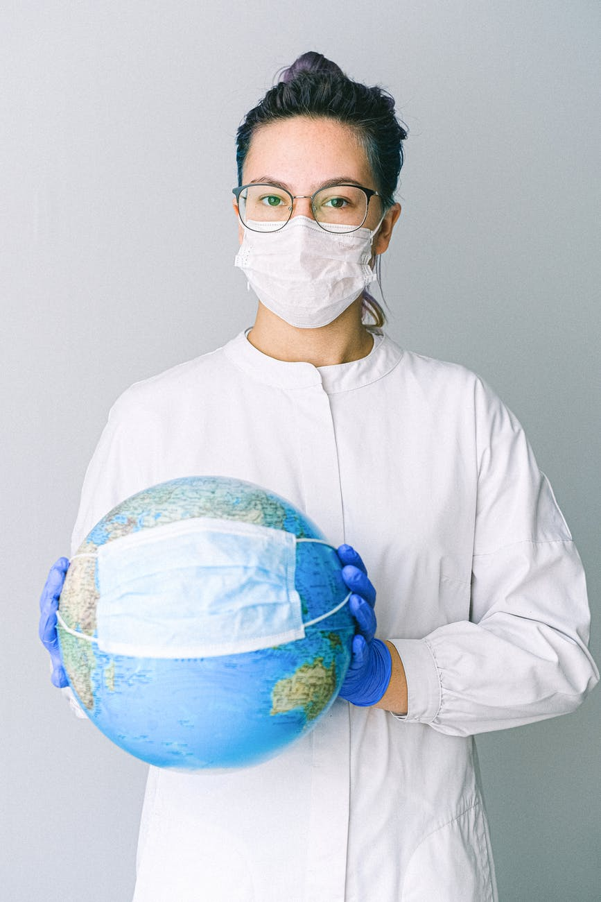 person with a face mask and latex gloves holding a globe that also has a face mask